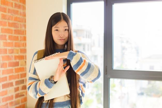 Jonge aziatische vrouw die ernstig, streng, boos en ontevreden kijkt en time-outteken maakt