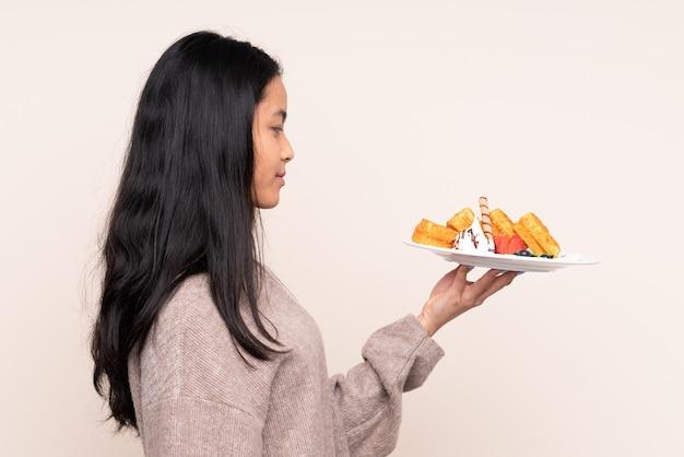 Jonge aziatische vrouw die geïsoleerde wafels eet