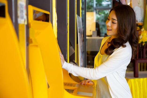 Jonge aziatische vrouw die geld met een kaart opneemt bij de automatische machine, wijfje dat zich bij atm van de bank bevindt