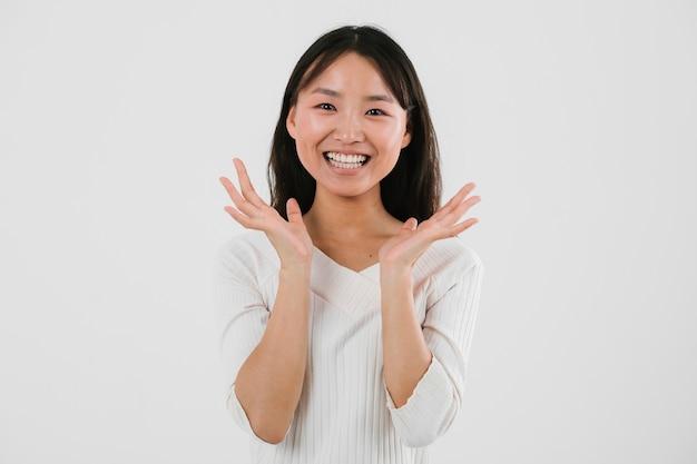 Jonge aziatische vrouw die gelukkig kijkt