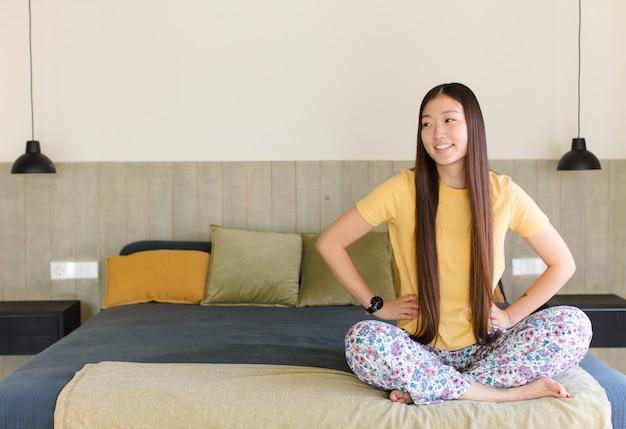 Jonge aziatische vrouw die gelukkig, vrolijk en zelfverzekerd kijkt, trots glimlacht en met beide handen op de heupen naar kant kijkt