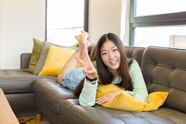 Jonge aziatische vrouw die gelukkig, zorgeloos en positief glimlacht en kijkt, overwinning of vrede met één hand gebaart