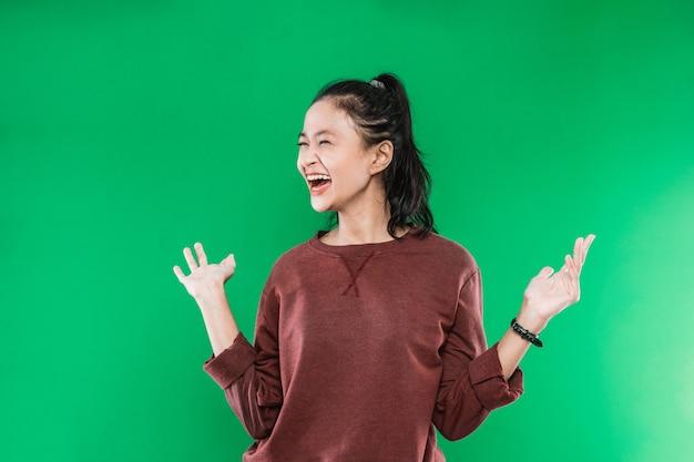 Jonge aziatische vrouw die gelukkige wijd-open mond uitdrukt die naast kijkt terwijl de handpalmen open stijgen geïsoleerd op groene achtergrond