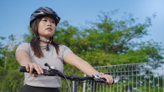Jonge aziatische vrouw die geniet van fietsen in de zomerochtend