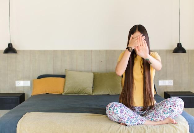 Jonge aziatische vrouw die gezicht bedekt met hand en andere hand naar voren zet om te stoppen, foto's of afbeeldingen weigert