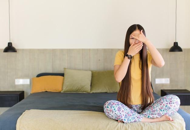 Jonge aziatische vrouw die gezicht met beide handen bedekt, afbeeldingen weigert of foto's verbiedt