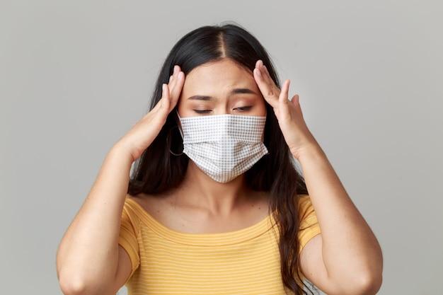 Jonge aziatische vrouw die gezichtsmasker draagt dat zichzelf beschermt tegen covid19