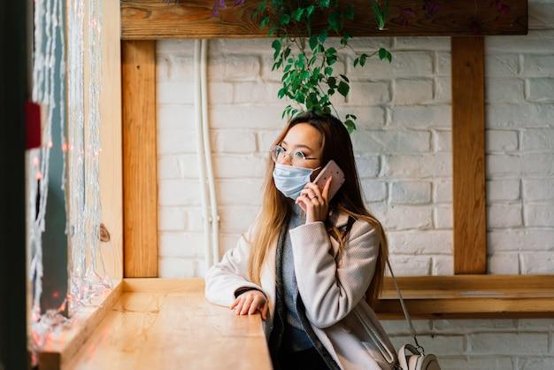 Jonge aziatische vrouw die gezichtsmasker draagt, staat op een binnenlandse straat. nieuwe normale covid-19-epidemie
