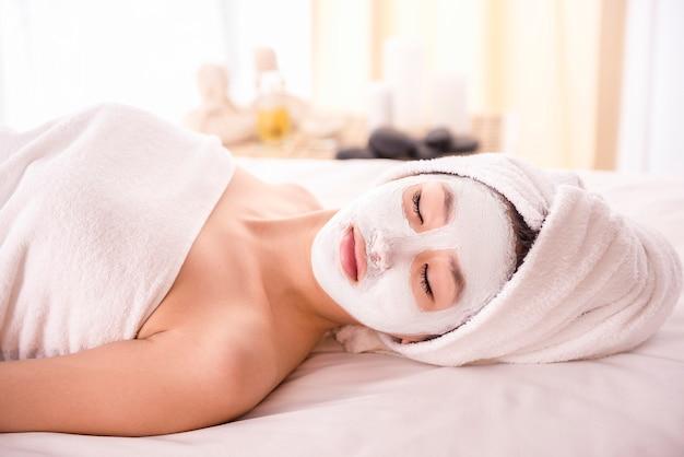 Jonge aziatische vrouw die gezichtsmasker ontvangt bij schoonheidssalon.