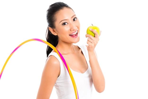 Jonge aziatische vrouw die gezond leeft en fruit eet