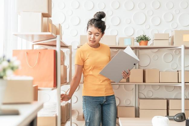 Jonge aziatische vrouw die goederen controleert op voorraadplank bij pakhuis