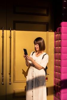 Jonge aziatische vrouw die haar smartphone buitenshuis controleert