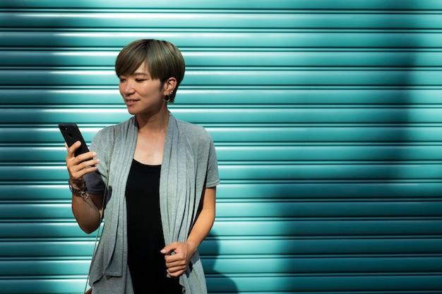 Jonge aziatische vrouw die haar telefoon buiten controleert