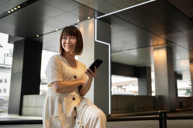 Jonge aziatische vrouw die haar telefoon controleert