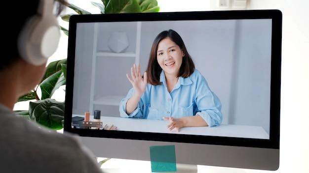 Jonge aziatische vrouw die haar vriend begroet door virtuele videoconferentie thuis, sociale afstand, telecommunicatie