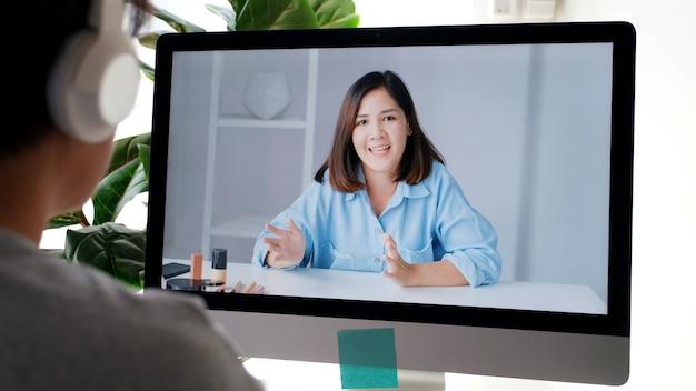 Jonge aziatische vrouw die haar vriend begroet via videoconferentie