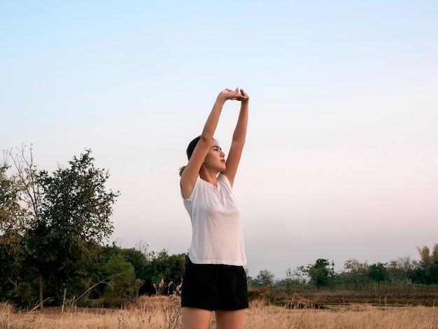 Jonge aziatische vrouw die haar wapens op blauwe hemel dichtbij grasgebied uitrekt