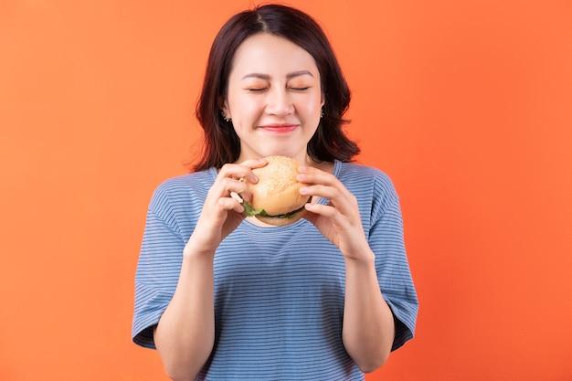 Jonge aziatische vrouw die hamburger op sinaasappel eet