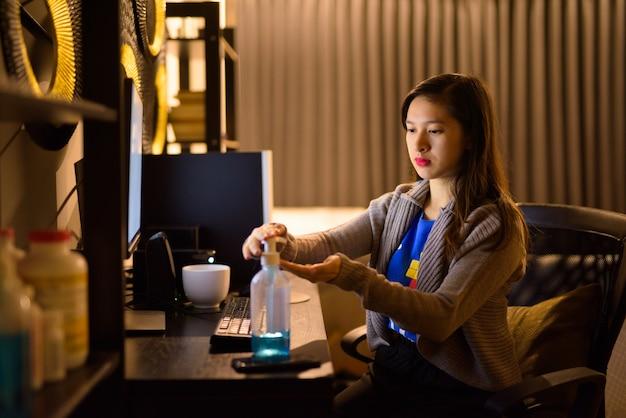 Jonge aziatische vrouw die handdesinfecterend middel gebruikt terwijl 's nachts vanuit huis werkt