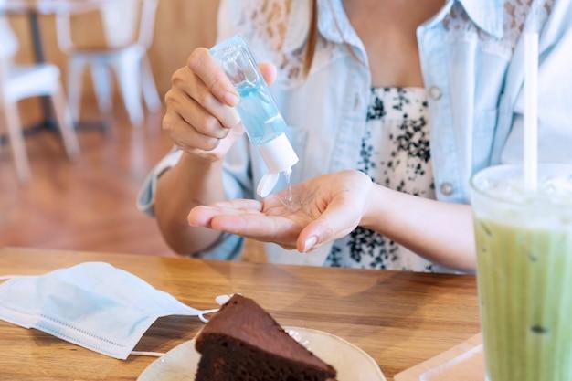 Jonge aziatische vrouw die handdesinfecterend middel op haar hand toepast alvorens in koffie te eten voor bescherming tegen besmettelijk virus