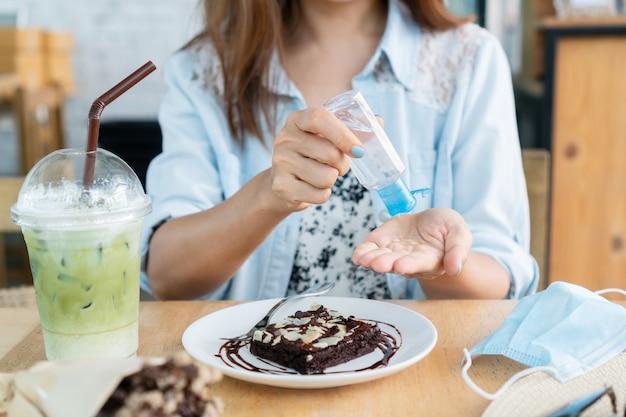 Jonge aziatische vrouw die handdesinfecterend middel op haar hand toepast alvorens in koffie voor bescherming tegen besmettelijk virus te eten