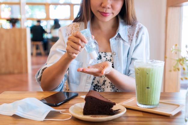 Jonge aziatische vrouw die handdesinfecterend middel toepast om haar hand schoon te maken alvorens te eten. gezondheidszorg concept.