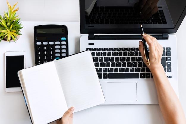 Jonge aziatische vrouw die het onderzoekswerk voor haar zaken met computerlaptop doen terwijl thuis het houden van notitieboekje, hoogste mening en exemplaarruimte