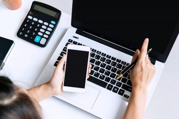 Jonge aziatische vrouw die het onderzoekswerk voor haar zaken met computerlaptop doet terwijl het houden van slimme telefoon