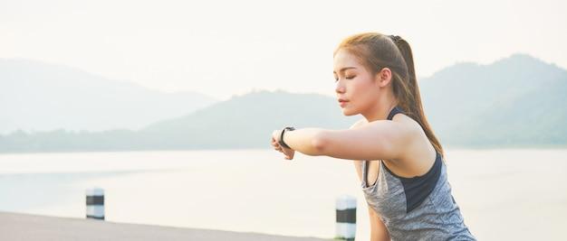 Jonge aziatische vrouw die het sportenhorloge kijkt en haar prestaties controleert. op de weg.