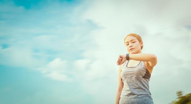 Jonge aziatische vrouw die het sportenhorloge kijkt en haar prestaties na looppas jogging controleert.