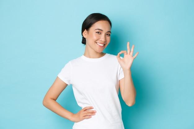 Jonge aziatische vrouw die het toevallige t-shirt stellen draagt