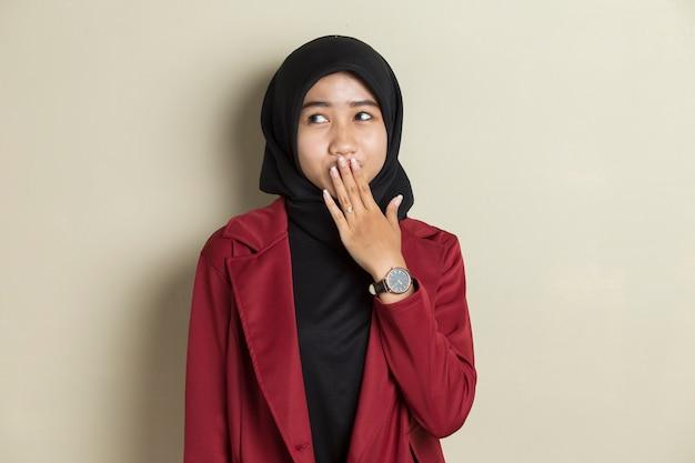 Jonge aziatische vrouw die hijab draagt die geschokt mond bedekt met handen voor fout. geheim concept.