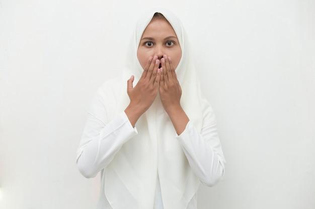 Jonge aziatische vrouw die hijab draagt die geschokt mond bedekt met handen voor fout