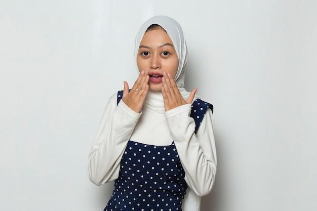 Jonge aziatische vrouw die hijab draagt, geschokt die mond bedekt met handen voor fout geheim concept