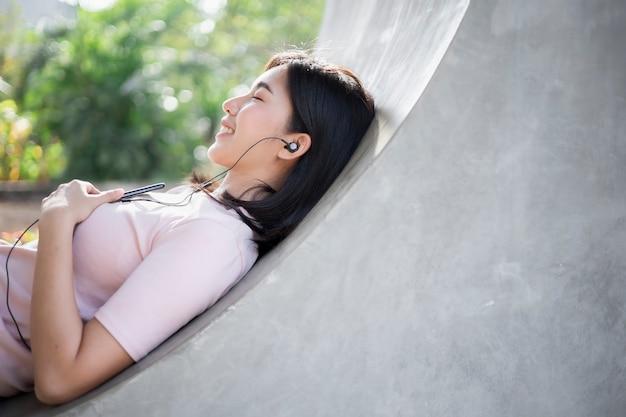 Jonge aziatische vrouw die hoofdtelefoons draagt en aan muziek op haar mobiele telefoon luistert.