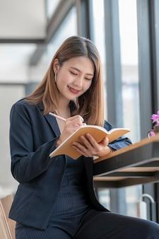 Jonge aziatische vrouw die in blauw kostuum op notitieboekje schrijven terwijl het zitten bij houten tegenlijst in co-werkruimte.