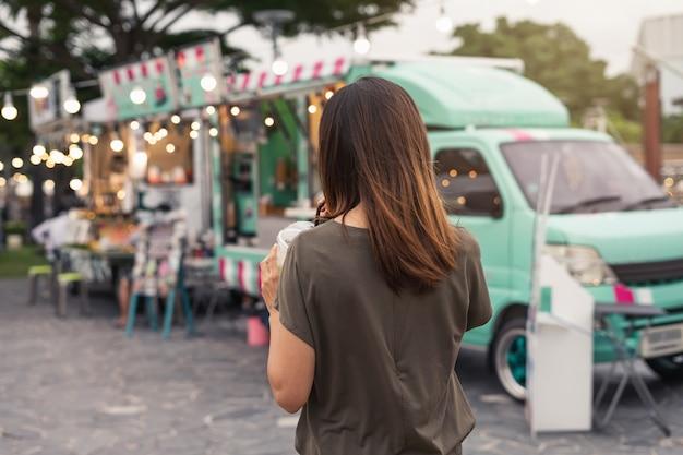 Jonge aziatische vrouw die in de markt van de voedselvrachtwagen loopt