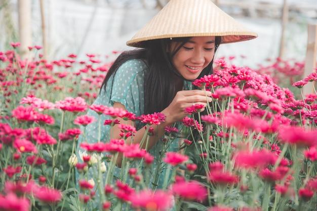 Jonge aziatische vrouw die in het landbouwbedrijf van kamillebloemen werkt