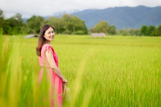 Jonge aziatische vrouw die in het padieveld geniet van