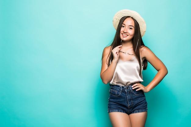Jonge aziatische vrouw die in hoed en zonnebril turkooise achtergrond glimlachen