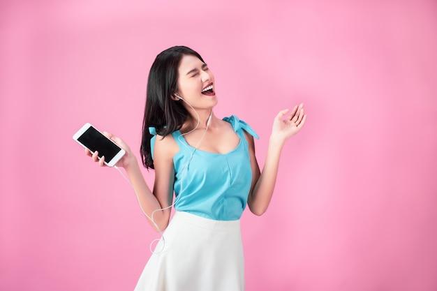 Jonge aziatische vrouw die in oortelefoons aan muziek en het dansen luistert