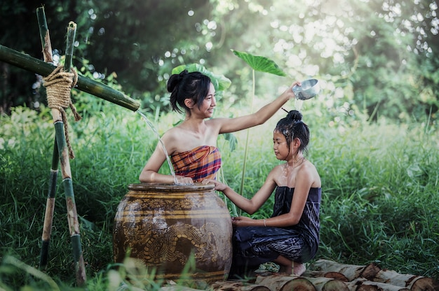 Jonge aziatische vrouw die in tropisch de zomer baadt bij plaatsplatteland van thailand