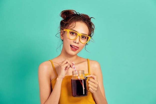 Jonge aziatische vrouw die in vrijetijdskleding een kop soda over blauw houdt