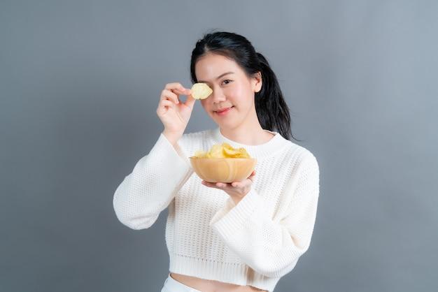 Jonge aziatische vrouw die in witte sweater chips op grijze muur eet