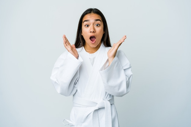 Jonge aziatische vrouw die karate doet die op witte verrast en geschokt muur wordt geïsoleerd