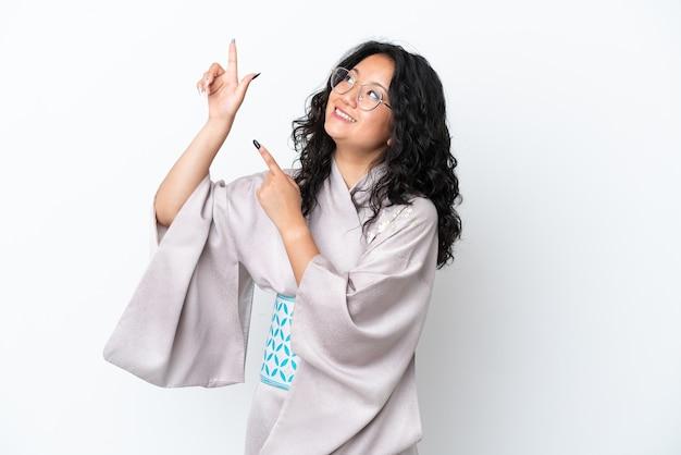 Jonge aziatische vrouw die kimono draagt die op witte achtergrond wordt geïsoleerd en met de wijsvinger wijst een geweldig idee