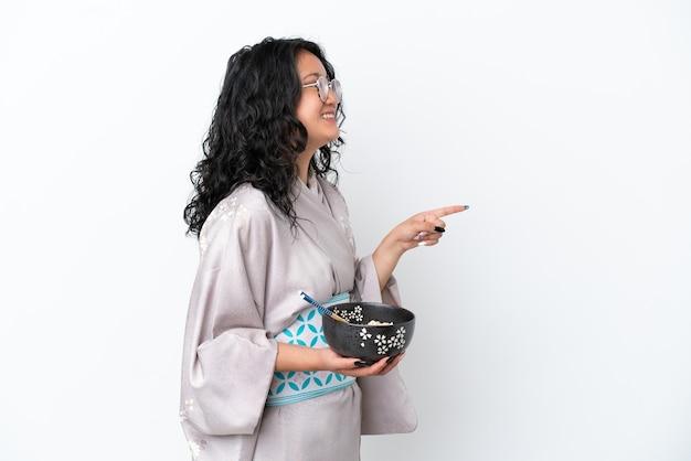 Jonge aziatische vrouw die kimono draagt die op witte achtergrond wordt geïsoleerd en naar de zijkant wijst om een product te presenteren terwijl ze een kom noedels met eetstokjes vasthoudt
