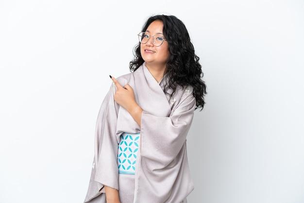 Jonge aziatische vrouw die kimono draagt die op witte achtergrond wordt geïsoleerd en naar de zijkant wijst om een product te presenteren