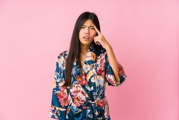 Jonge aziatische vrouw die kimonopyjama's draagt die een teleurstellingsgebaar met wijsvinger tonen.