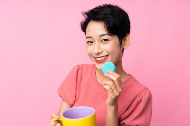 Jonge aziatische vrouw die kleurrijke franse macarons en een kop van melk houdt